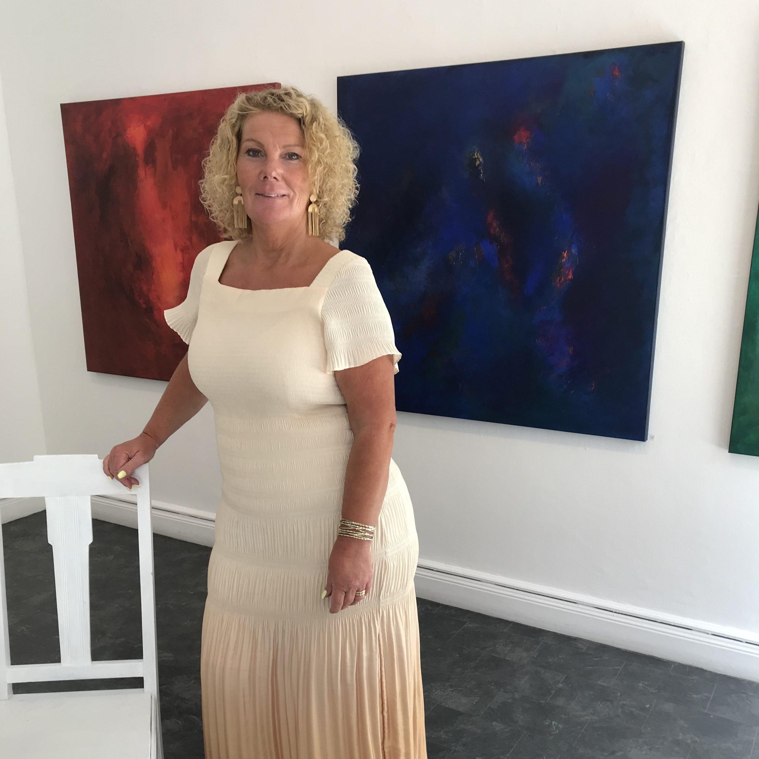 Ewa Kinnunen står i sitt galleri iklädd beigevit lång klänning och har ljust långt lockigt hår. Bakom syns två tavlor, en blå och en röd.