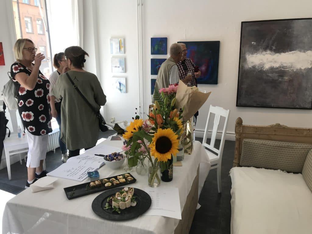 Besökare på versnissage med Ewa kinnunen. 5 personer syns i bild som står och pratar och i bakgrunden syns tavlor på väggen. I förgrunden finns ett bord med blommor och tilltugg på.